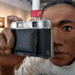 Sculpture of a man holding up his photo camera and looking through the viewfinder.