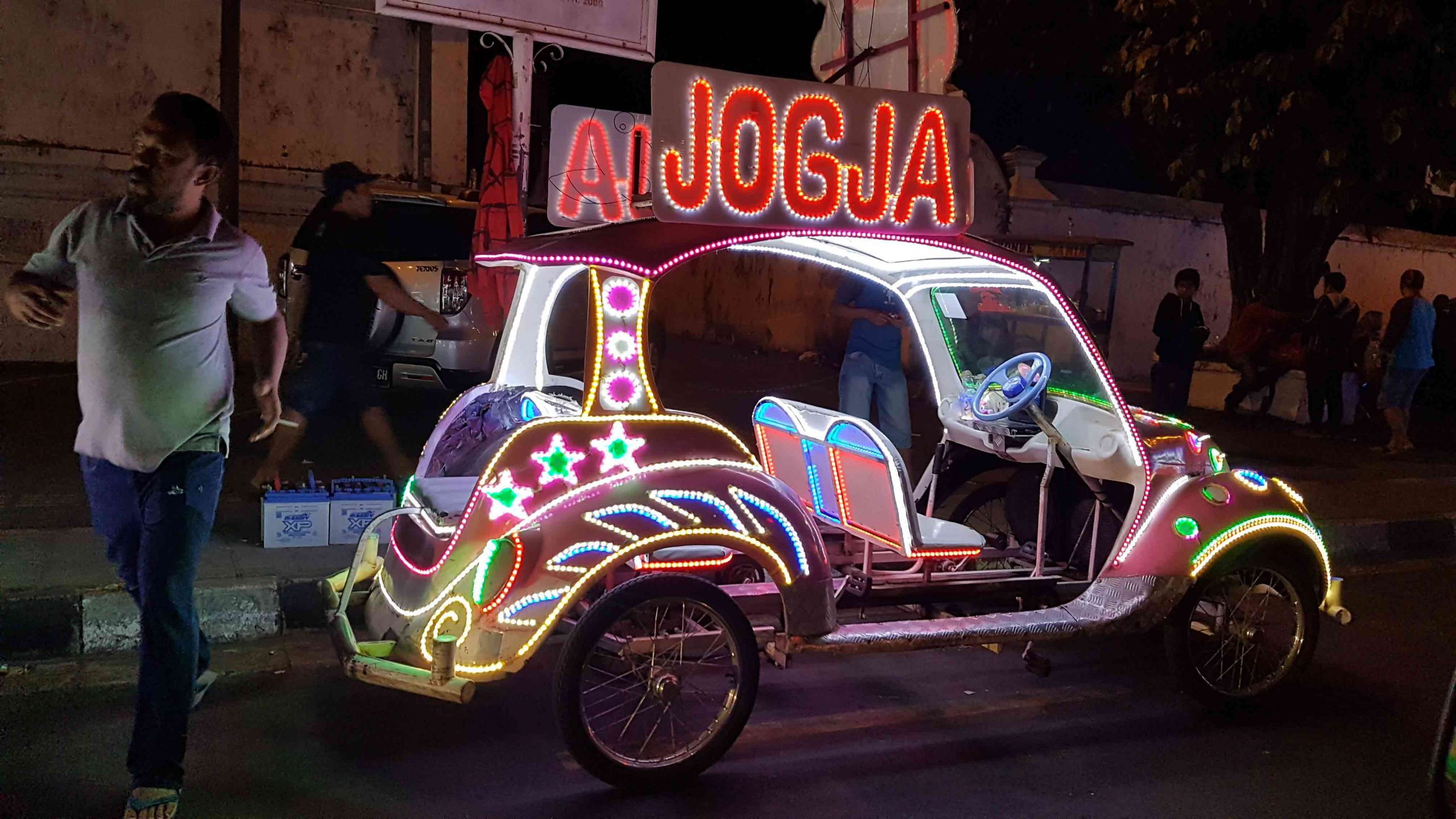 An motorized buggy decked in lights with additional seats and an illuminated JOGJA sign on the roof