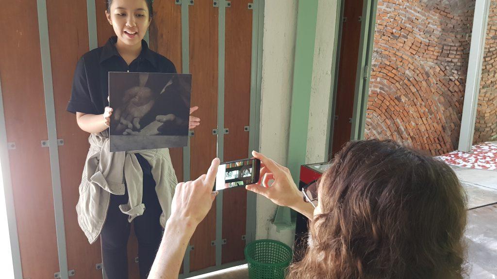 Seorang pria mengangkat ponselnya untuk menangkap penanda AR - foto memperlihatkan tangan terbuka / A man holds up his mobile phone to frame the AR marker - a square photograph of open hands.