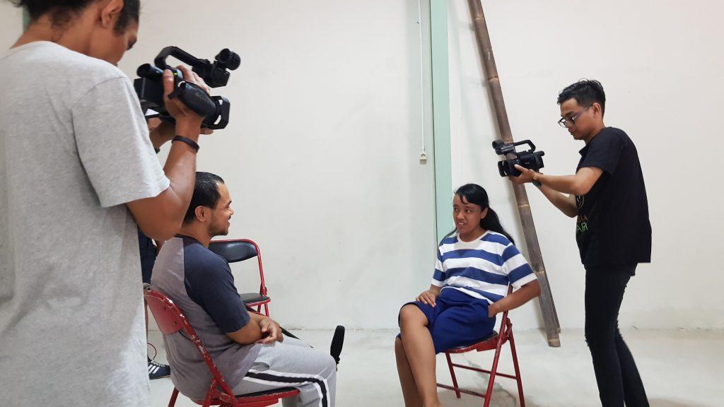 Dua aktor duduk saling berhadapan sementara dua kru kamera mengambil gambar dari sudut yang berlawanan / Two actors sit facing each other while two camera people shoot the scene from opposite angles.