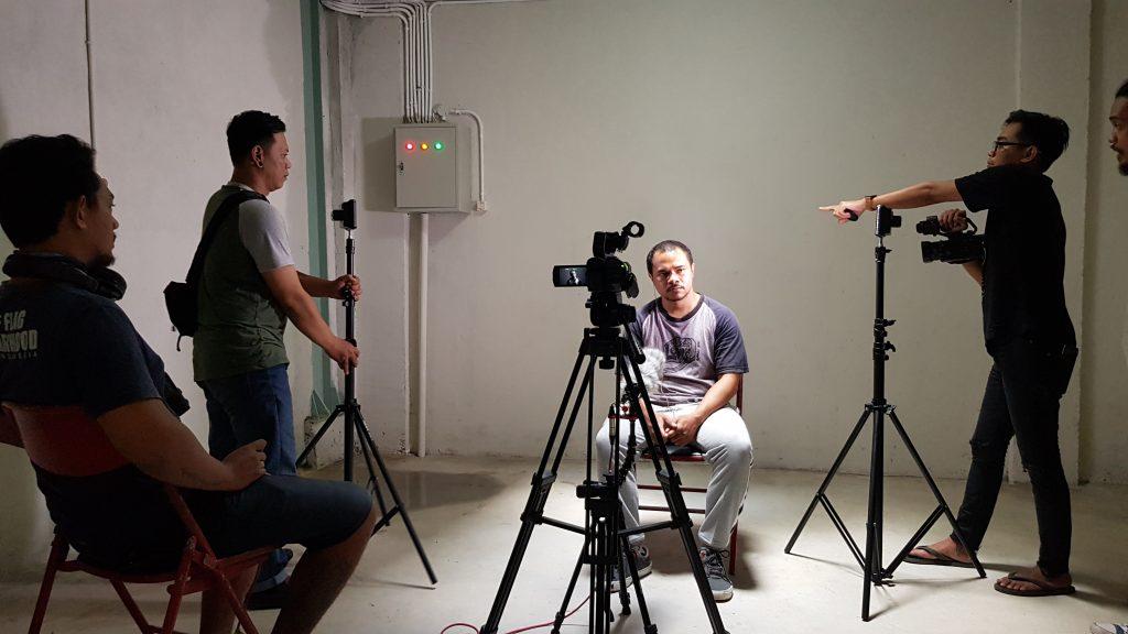 Kru kamera mengelilingi aktor yang duduk / Camera crew surround a seated actor.