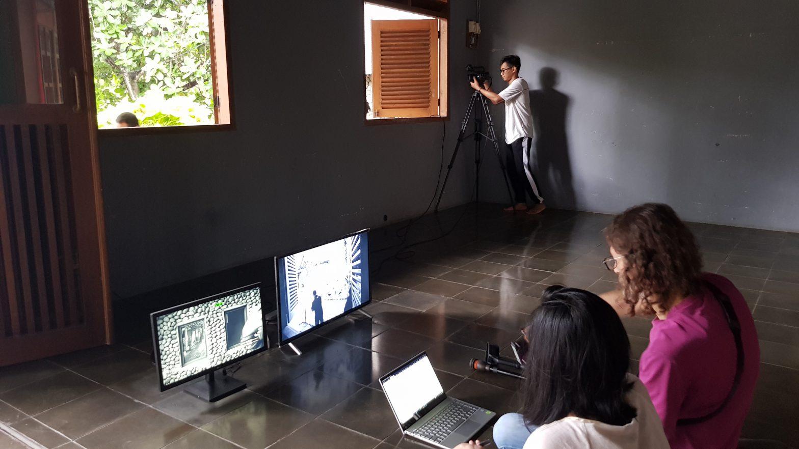 Dua orang duduk di lantai di depan monitor sementara seorang kru kamera mengambil gambar jendela yang terbuka / Two people sit on the floor in front of monitors while a camera person shoots out an open window.