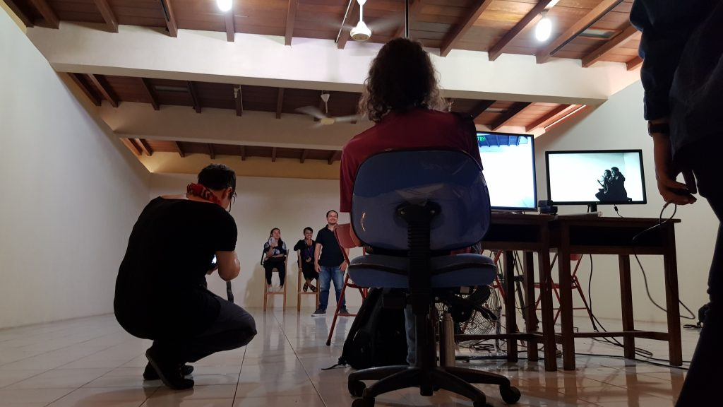 Seorang sutradara duduk di depan monitor sementara sebuah adegan sedang diperankan / A director sits in front of monitors while a scene is acted out.