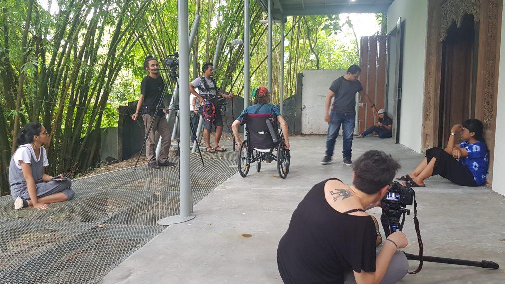 Sutradara dan kru kamera mengambil gambar para aktor yang sedang duduk di pintu teras luar / Director and camera crew shoot actors sitting in doorway of an outdoor terrace.