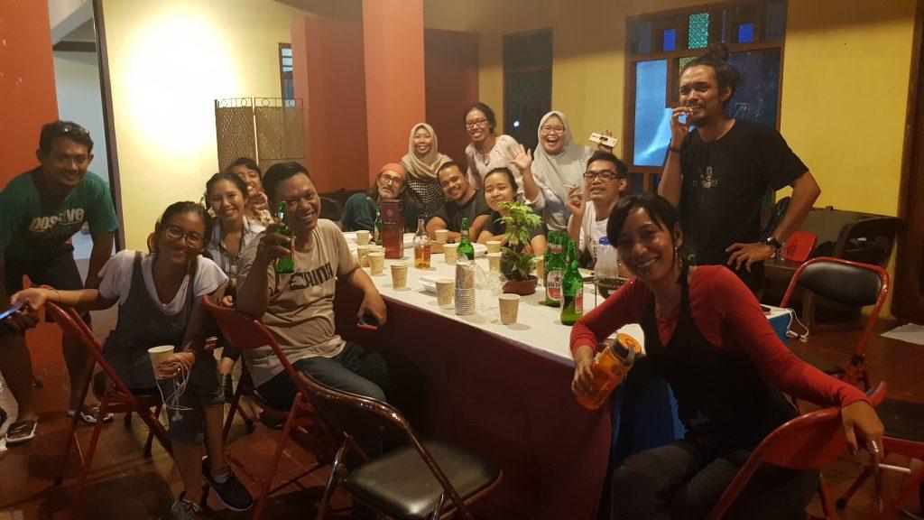 Aktor dan kru berpesta di sekitar meja dengan makanan dan minuman / Cast and crew celebrate around a table with food and drinks.