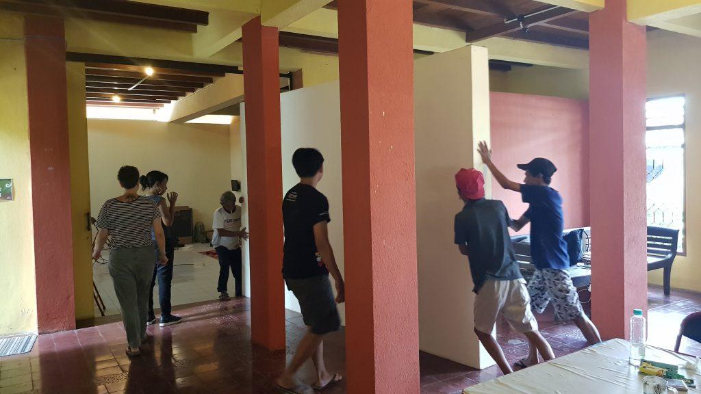 Orang-orang memindahkan sekat ke ruang galeri / People move a partition into the gallery space.