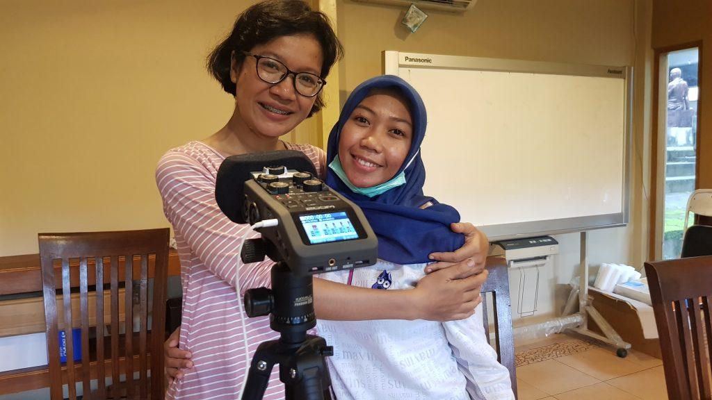 Dua wanita berpelukan di depan sebuah perekam audio /Two women hug in front of an audio recorder.