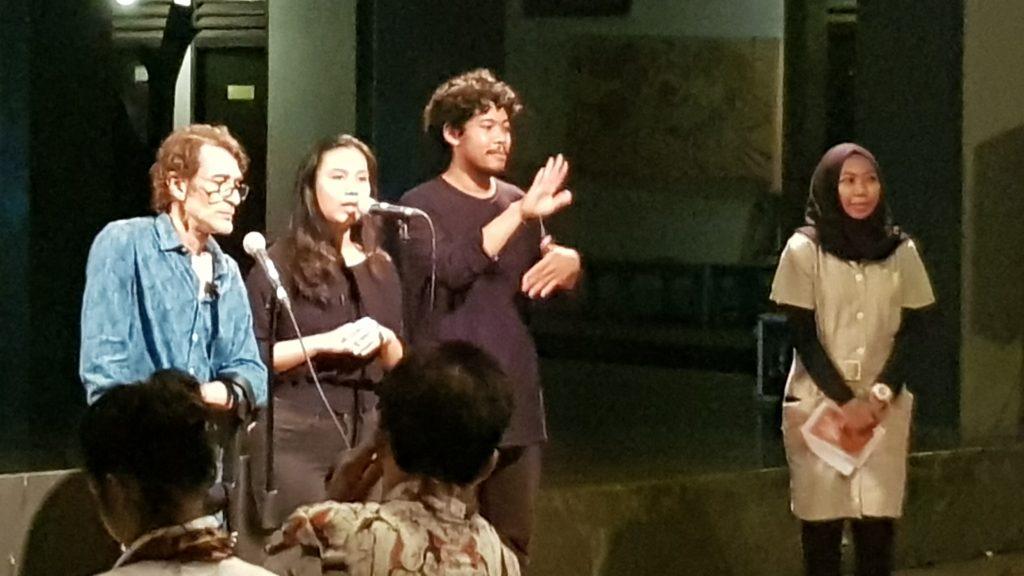 Sutradara Caglar Kimyoncu berdiri di depan mikrofon di samping penerjemah, pembawa acara, dan penerjemah Bahasa Isyarat Indonesia / Director Caglar Kimyoncu stands before a microphone beside a translator, presenter, and Indonesian Sign Language interpreter.