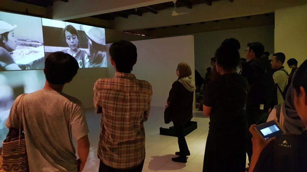 Kerumunan orang menonton proyeksi video dengan layar terbagi / A crowd watches the split screen video projection