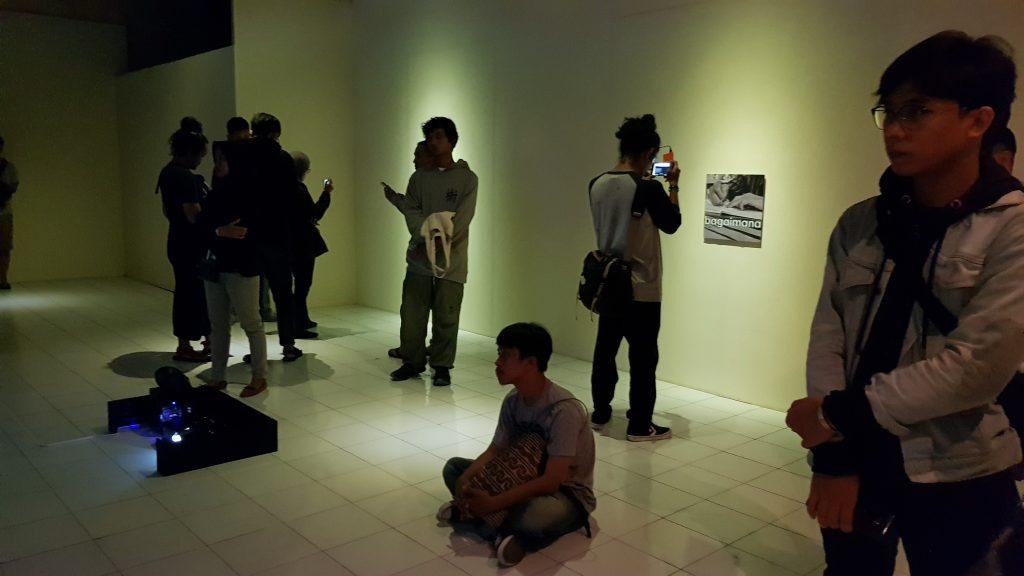 Di ruang galeri, hadirin melihat video dan proyeksi sementara salah satu menangkap penanda AR di ponselnya / In the gallery space, viewers look at the videos and projections while one frames an AR marker on his mobile phone.