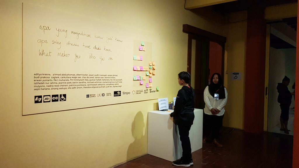 Seorang anak muda berdiri di depan tembok yang berisi respons di catatan-tempel yang ditulis oleh orang-orang / A young person stands before a wall with post-it note responses written by the public.