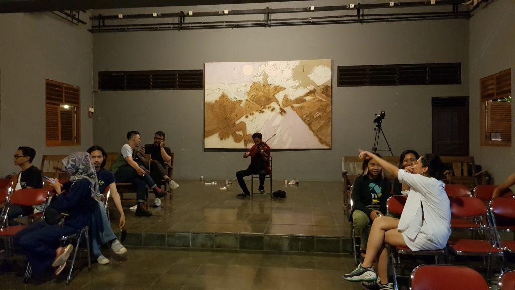 Seorang pemain biola memainkan lagu untuk para peserta di depan sebuah lukisan oleh Bagong /A violin player for audience members before a painting by Bagong.