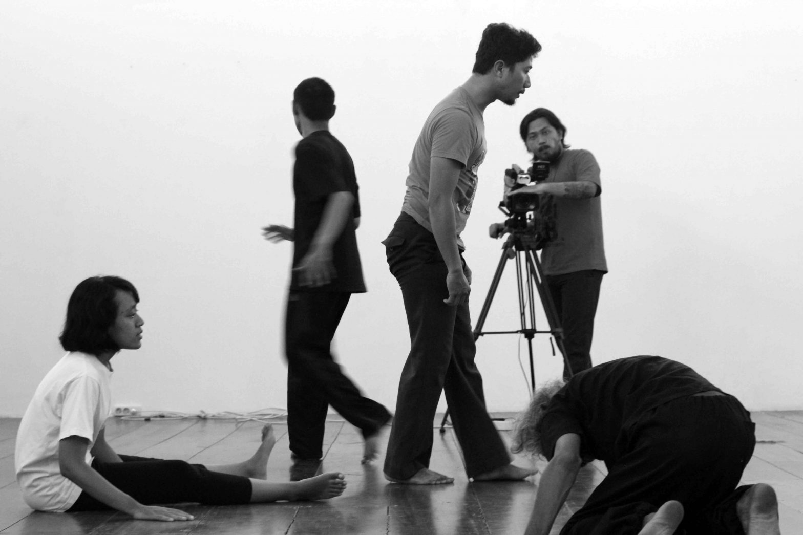 A cameraman watches performers in various movement poses.