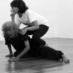A woman performer with forefinger held up for silence kneels on the back of a scowling male performer.