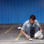 A man squats on the street repairing the sidewalk with a bucket of cement and trowel.