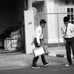 Two boys in school uniform stand in the street.