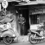 Photo shows a man standing in the doorway of a taxi stand beside two motorbikes.