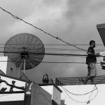 Cityscape shows a man standing on a roof beside a satellite dish.