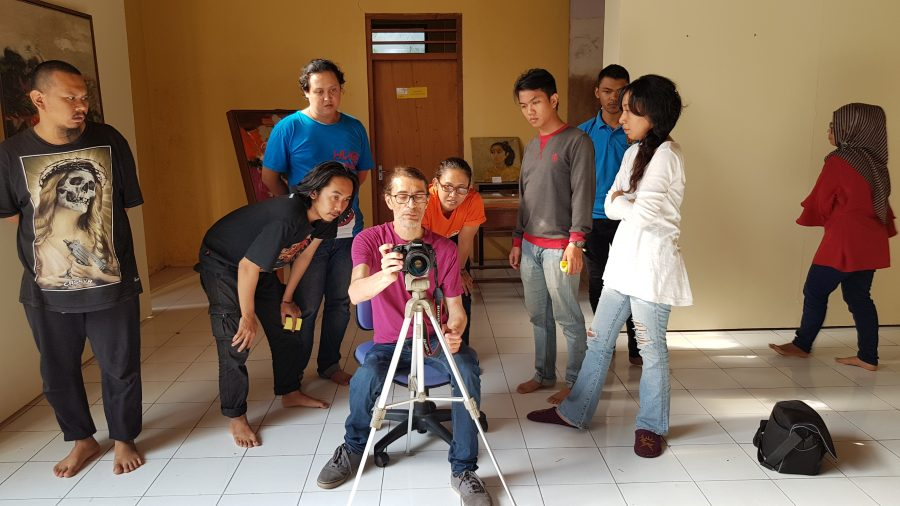A man sits before a camera on a tripod, with other people gathered round.