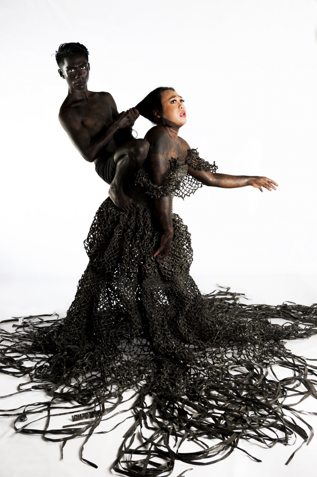 A woman dressed in black net-like fabric with oily substance covering her body grimaces as a naked man mounted on her back pulls back her hair.