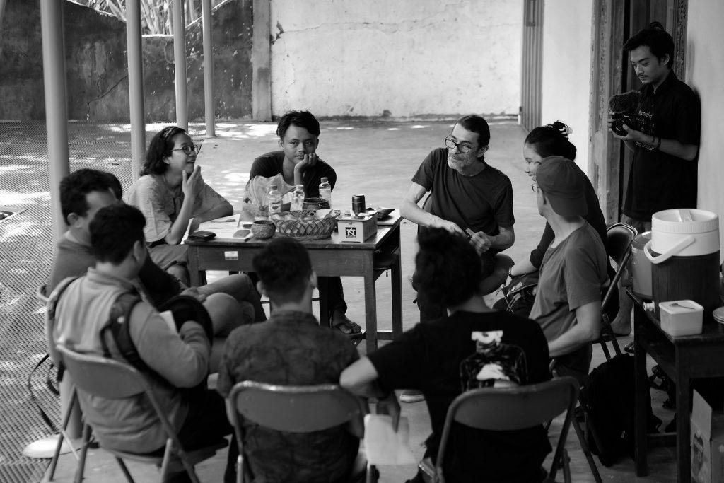 Pertemuan produksi dengan Caglar dan kru yang duduk di sekitar meja / Production meeting with Caglar and crew sitting around a table
