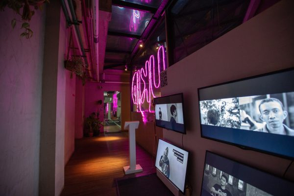 Exhibition view of video installation with multiple screens showing black and white images of young men and women.