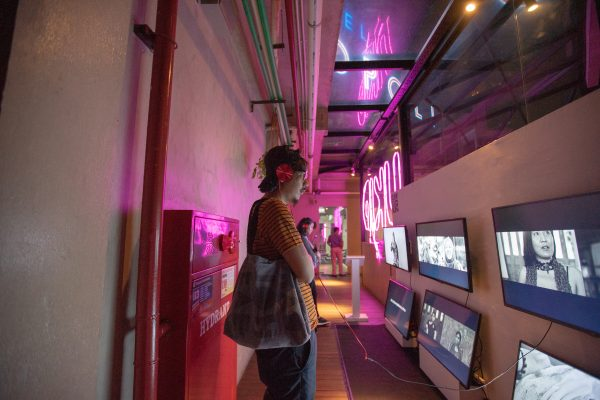 An audience member wears headphones attached to a video monitor at a video art installation.