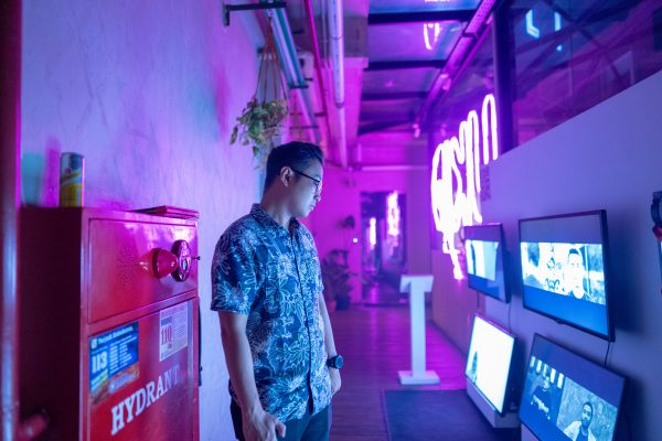 A man looks at a video installation with multiple screens.