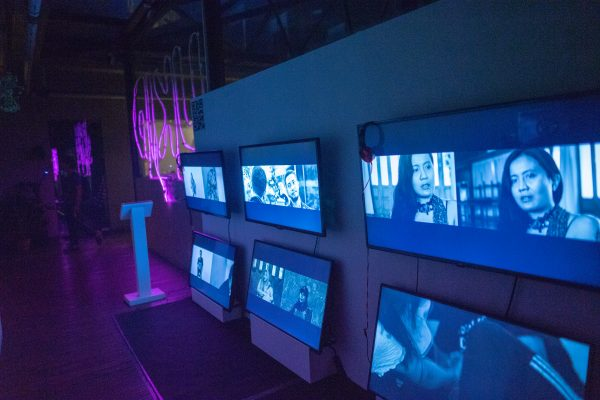 Colour photo shows installation view of video exhibition with multiple screens showing split screen images of men and women.