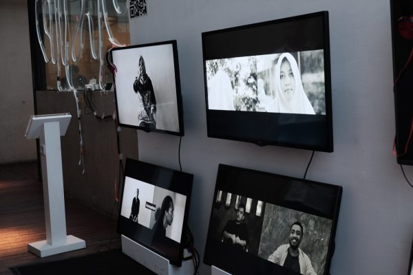 Exhibition view of a video installation shows multiple screens with black and white images of men and women.