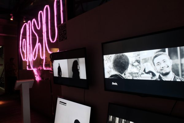 An installation view of an exhibition shows video screens, two with split screen images of young people, beside a neon sculpture.