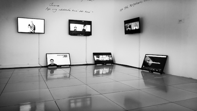 Exhibition view of video installation with monitors hung on walls and resting on the floor.