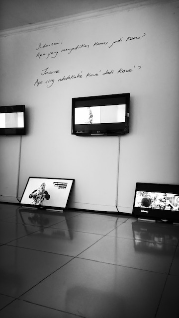 Exhibition view of video installation with monitors hung on wall and resting on the floor, beneath words handwritten on the wall.