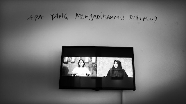 """Monitor hung on the wall shows split screen image of young man and young woman, with the words """"Apa Yang Menjadikanmu Dirimu?"""" written on the wall above it."""