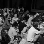 A group of people sits on the floor, facing forward and listening.