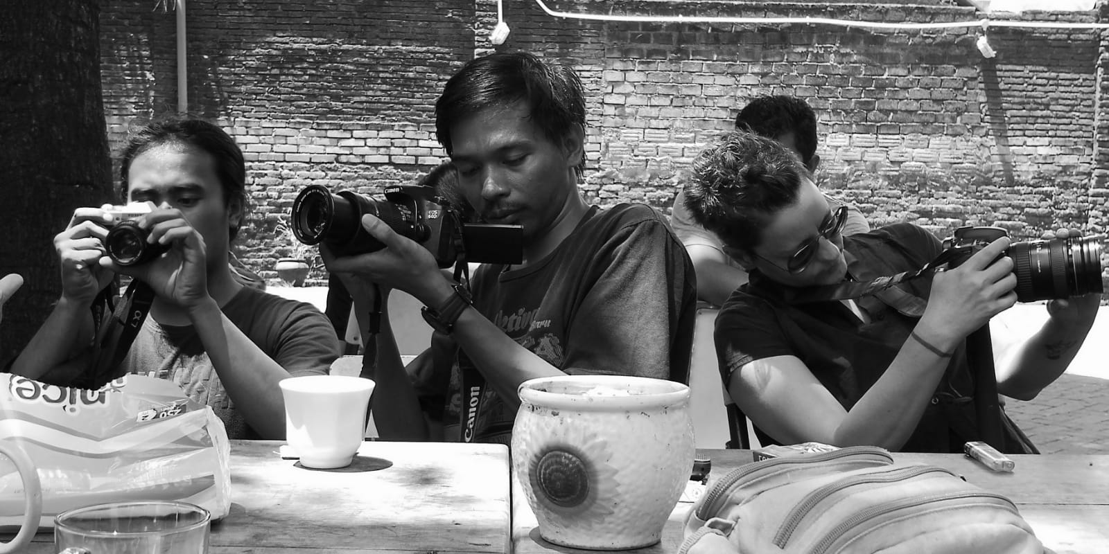 Three seated people look through their cameras.