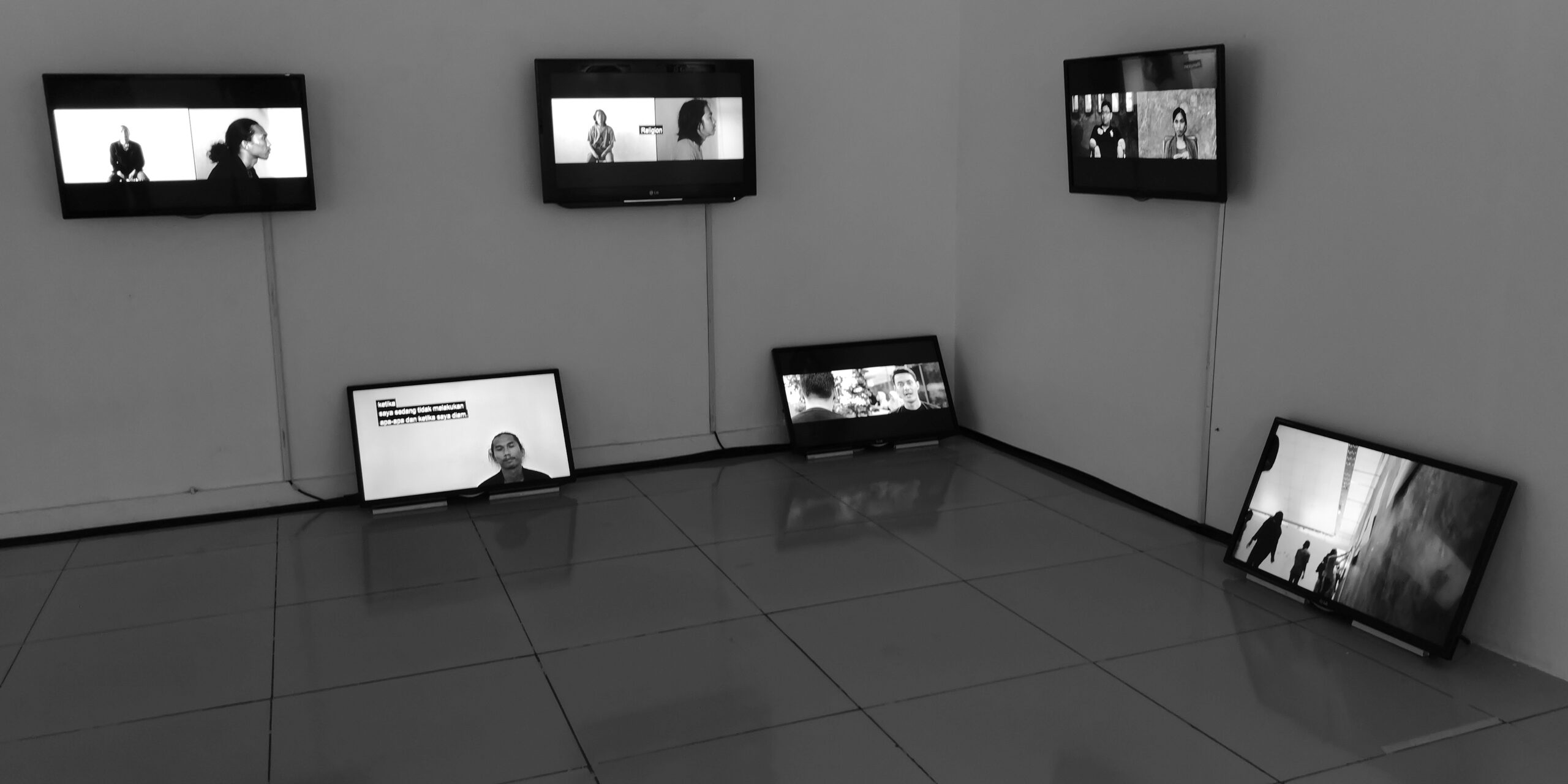 Exhibition view of video installation with six monitors hung on the wall and resting on the floor.