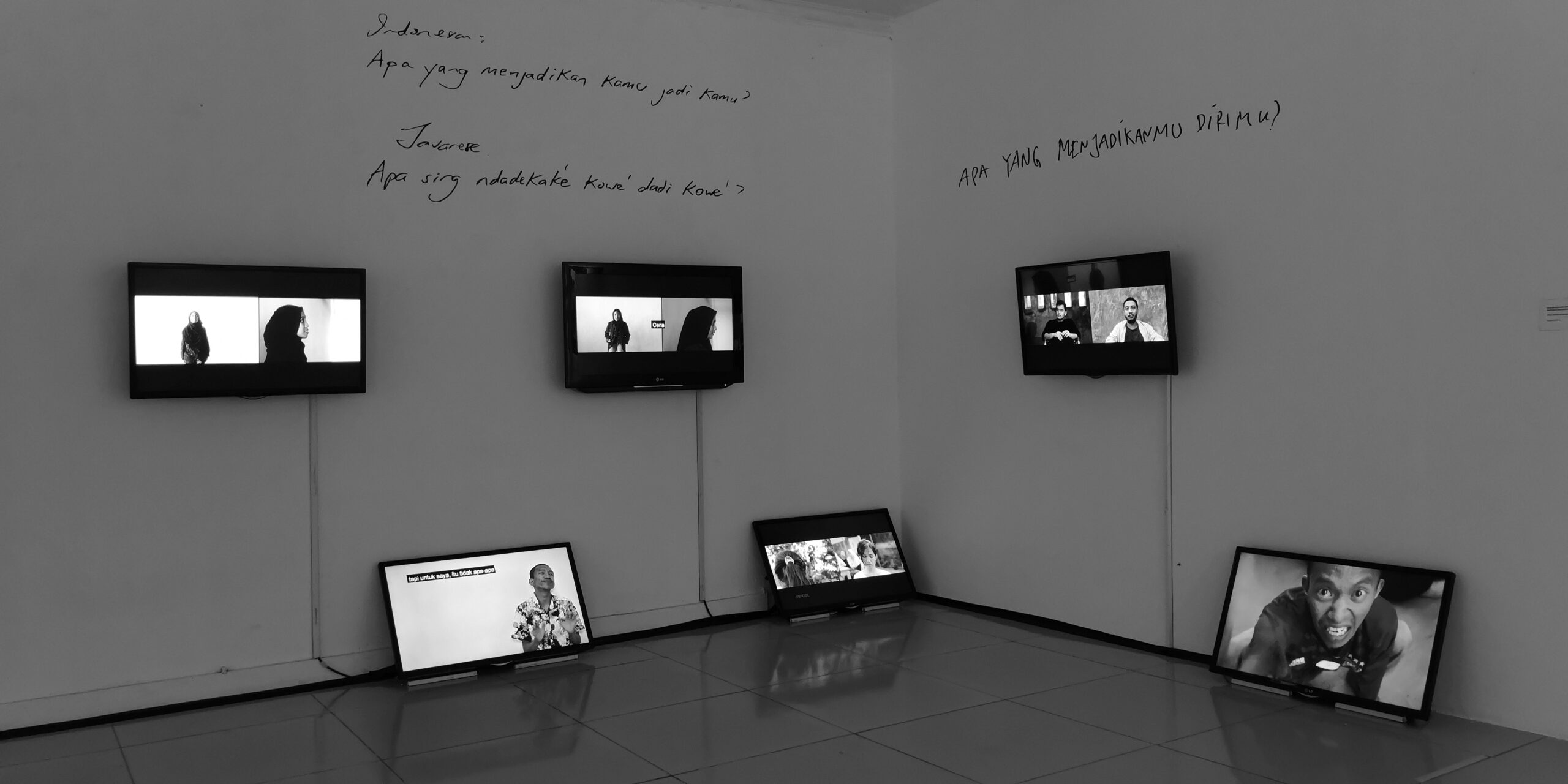 Exhibition view of video installation with monitors hung on walls and resting on the floor, as well as words written on the wall.