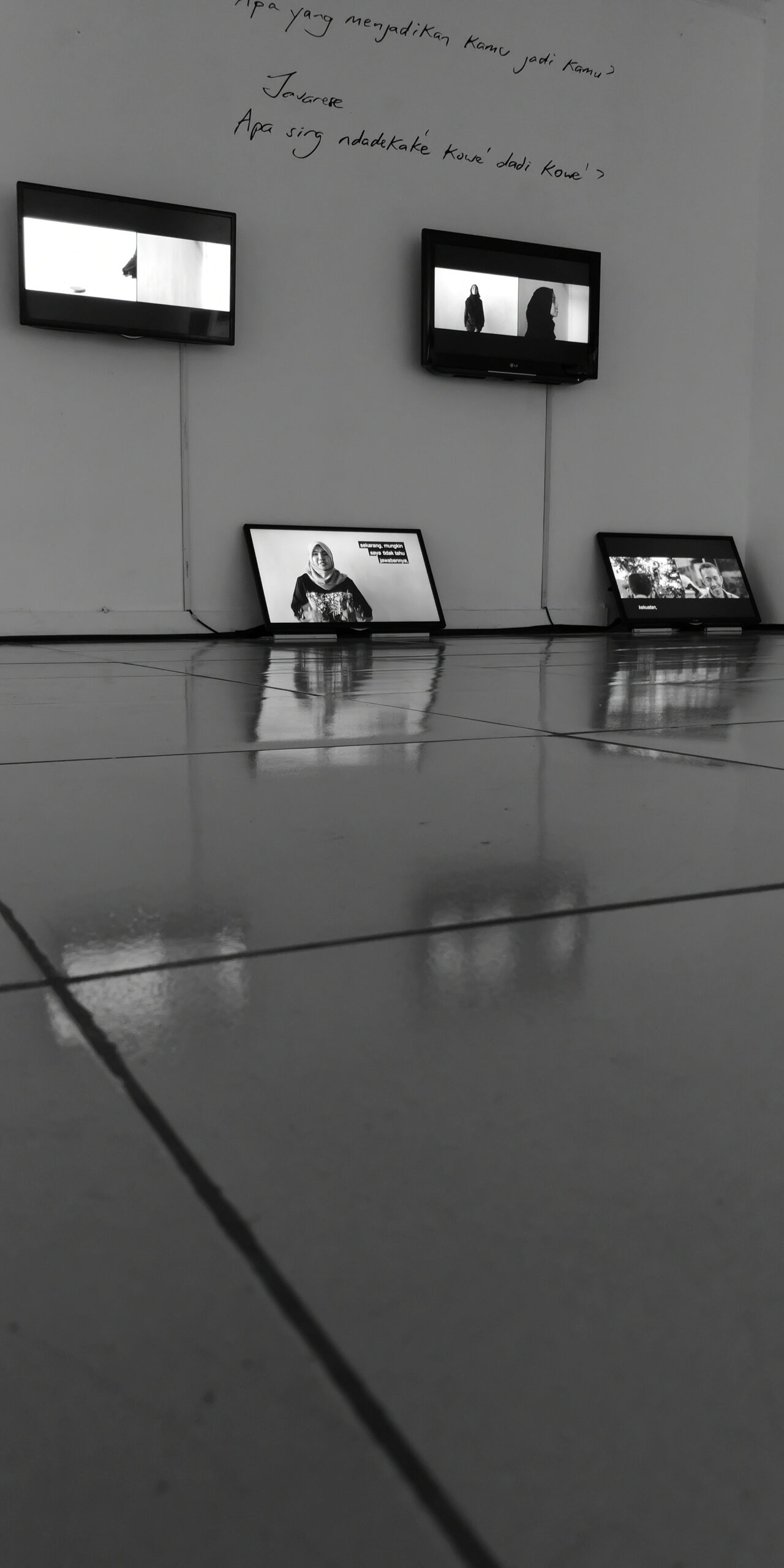 Exhibition view of video installation with monitors hung on the wall and resting on the floor.