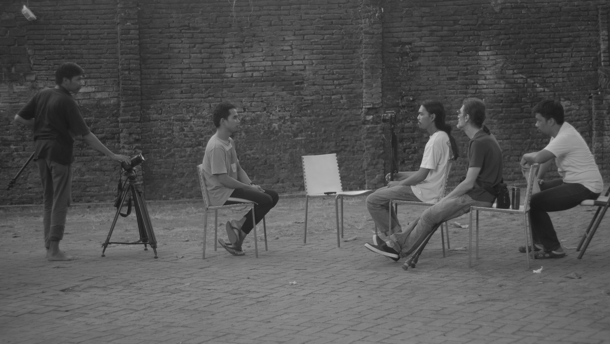 A photographer films a scene of two seated men, while two other people observe.